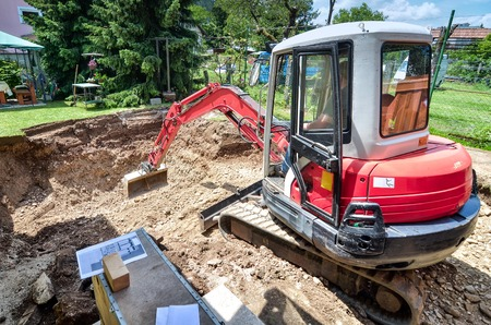 A family house is being rebuilt with the help of an excavator