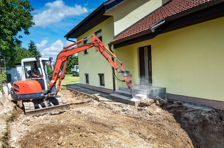 foreclosed: A house is being forclosed and demolished with a crusher Stock Photo