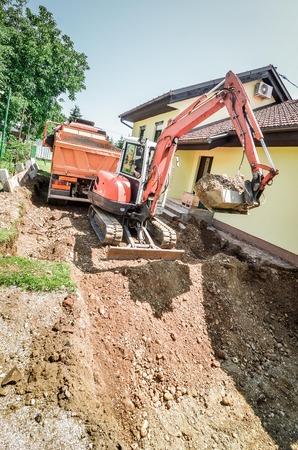 家を再構築し、ショベルで土を掘り
