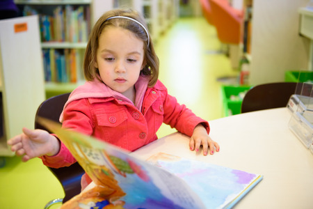 Little girl is browsing a book in the library. A child is looking at the books in the library deciding which one to take home. Children creativity and imagination. Stock Photo