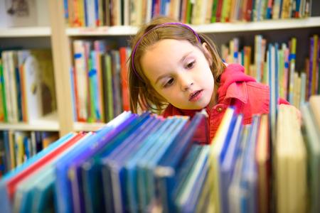 дети: Маленькая девочка выбирает книгу в библиотеке. Ребенок смотрит на книги в библиотеке решить, какой из них взять домой. Дети творчество и воображение.