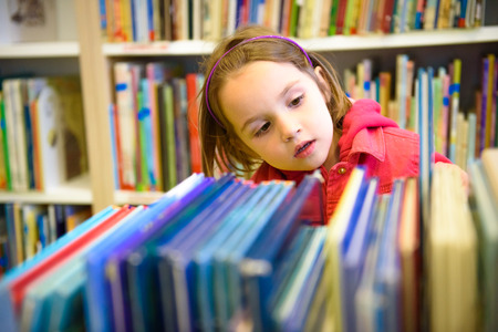 Little girl is choosing a book in the library. A child is looking at the books in the library deciding which one to take home. Children creativity and imagination.
