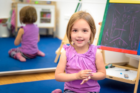 Little child is drawing with pieces of color chalk on the chalk board. Girl is expressing creativity and looking at the camera, smiling in a nursery, classroom or playroom. Concept of play, creativity, expression and learning photo