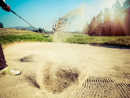 golf clubs: Golfer hitting out of a sand trap. The golf course is on the sand. Sand making splashes. Sun and sunshine in the background