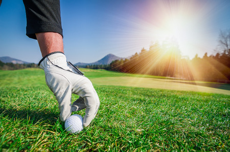Hand with a glove is placing a t golf ball on the ground.