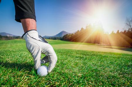 Hand met een handschoen is het plaatsen van golfbal op de grond. Stockfoto
