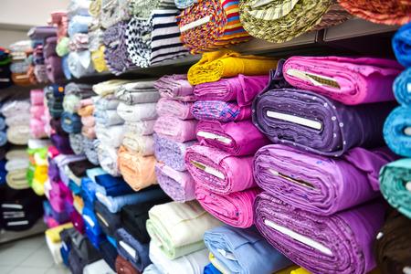 공장 상점에서 직물의 롤 및 섬유. 시장에 다 다른 색상과 패턴.