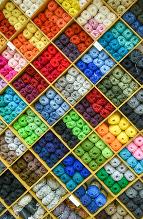 haberdashery: Yarns or balls and of wool are forming lovely colorful pattern. Accessories for haberdashery in a Fabric store shelves. Multi colored picture.