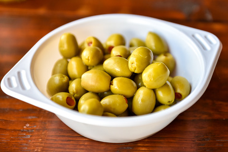 picknick: Plactic bowl of green olives on a wooden picknick desk