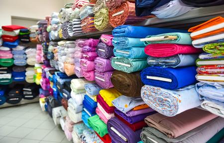 textil: Los rollos de tela y tejidos en una tienda de la fábrica. Múltiples colores y diseños diferentes en el mercado.