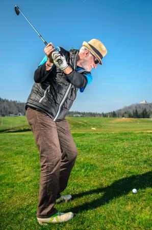 高齢者はゴルフです。アクティブな退職金。男は、形状に滞在するゴルフです。バック グラウンドで森の中で緑の草に