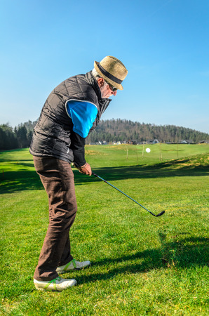 stay in the green: Senior citizen is playing golf. Active retirement. A man is golfing to stay in shape. On green grass with woods in the background