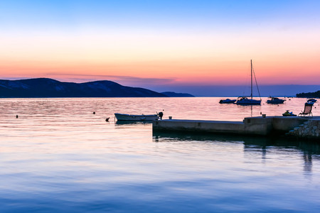 boat: Peaceful sunset or sunrise by the sea with boats and sailship. Landscape od small harbour village at dusk or dawn. Vacation, leisure and relaxation on the sea side. Stock Photo