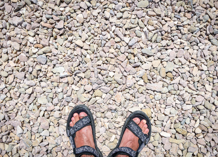 discovering: Travelers feet on stone paved road wearing sports sandals, discovering the unknown. Man feet on hard gravel.