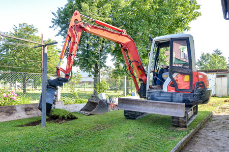 excavator: Rebuilding a house and digging dirt with excavator. Digger is starting to excavate the lawn.