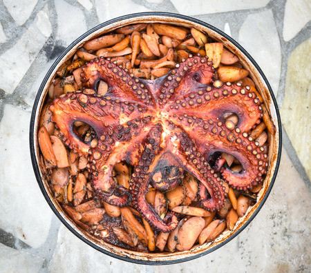 Preparing and Cooking of octopus in traditional Balkan CroatianGreek Mediterranean meal Peka in metal pots called sac sach or sache or a lid. Traditional roast of octopus with potatoes onions garlic tomato and spices. Standard-Bild