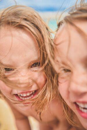 niñas gemelas: Muchachas gemelas están mirando a la cámara y riendo, haciendo selfie en día de verano en una playa tropical de arena - mar. Amigos, familiares y niños concepto. Foto de archivo