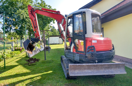 construction machinery: Rebuilding a house and digging dirt with excavator. Digger is starting to excavate the lawn.