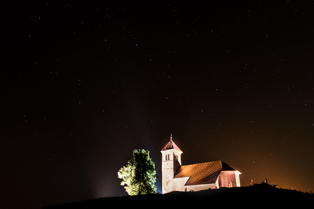 ursa: Nightscape with church and ursa major stars. Small church and tree on a hill are lit, with night sky full of stars and constellation ursa major.