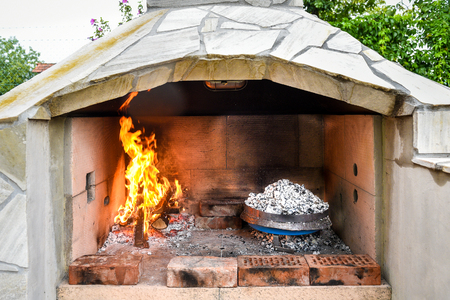 sac: Cooking of traditional Balkan Greek Mediterranean Croatian meal Peka in metal pots called sac sach or sache or a metal lid. Fireplace with open fire and burning coals. Stock Photo