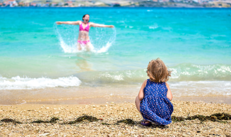 mother child: Mother and child having fun at the beach. Little girl is watching mother having fun in the sea. She is jumping and splashing water. Stock Photo