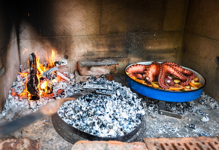 Preparing and Cooking of octopus in traditional Balkan CroatianGreek Mediterranean meal Peka in metal pots called sac sach or sache or a lid. Traditional roast of octopus with potatoes onions garlic tomato and spices.  Fireplace with open fire and burning