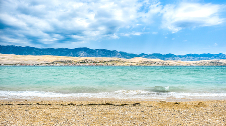 wind force: Strong wind bura is hitting coast of island Pag, making waves and splashes. Mountains Velebit in the background. Power and destructive force of wind. Adriatic sea - Croatia