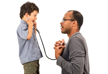stethoscope boy: Father and Son playing doctors with boy holding a stethoscope and listening to doctors heart as part of therapy. Stock Photo
