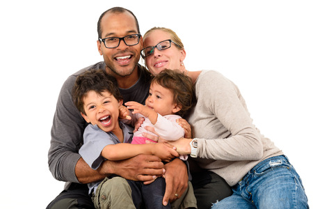 Happy interracial family is celebrating, laughing and having fun with Hispanic African American Father, Caucasian mother and Mulatto children son and daughter.  Isolated on white.