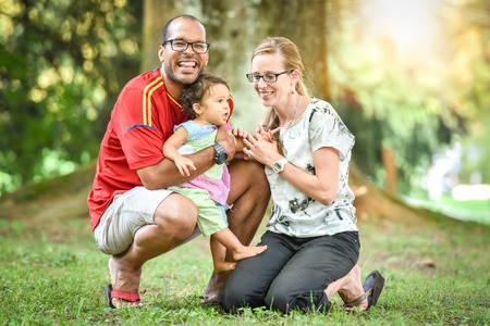 Happy interracial family is enjoying a day in the park. Little mulatto baby girl. Successful adoption. Diverse family in nature with sun in the back.
