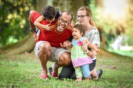 familia: Familia interracial feliz est� activo y disfrutar de un d�a en el parque. La ni�a mulata beb� y ni�o. Adopci�n exitosa. Familia diversa en la naturaleza con el sol en la espalda. Estilo de vida saludable.