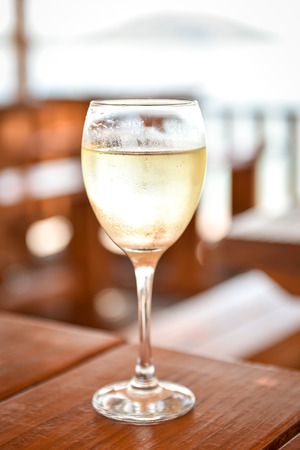 sauvignon: Glass of cold white wine on a wooden table in beach resort. Refreshing drink on the beach hut on vacation. Ice cold beverage with chardonnay or sauvignon with drops of moist and water for your enjoyment Stock Photo