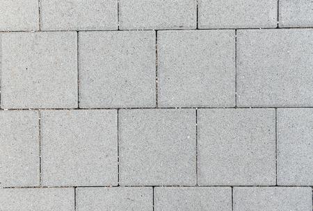 コンクリートや石畳の灰色の正方形の舗装スラブまたは石の床、壁またはパス。伝統的なフェンス、裁判所、裏庭や道路舗装。