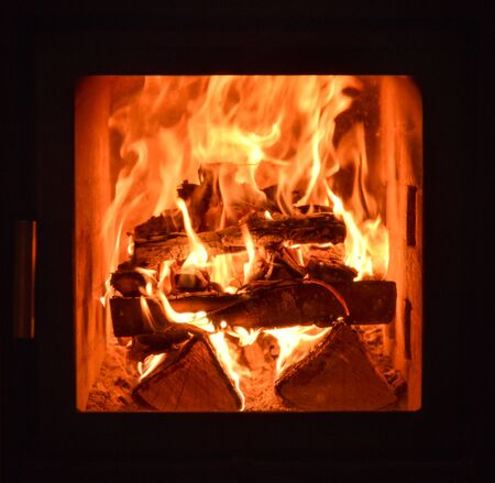 calor: Closeup of the inside of home traditional fireplace running on natural hard wood with flames and heat.