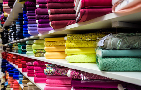 Rolls of fabric and textiles in a factory shop or  store or bazar. Multi different colors and patterns on the market. Industrial fabrics. 免版税图像 - 47546959