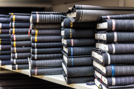 textile industry: Rolls of fabric and textiles in a factory shop or  store or bazar. Multi different fabric for men formal business suit on the market. Industrial fabrics.