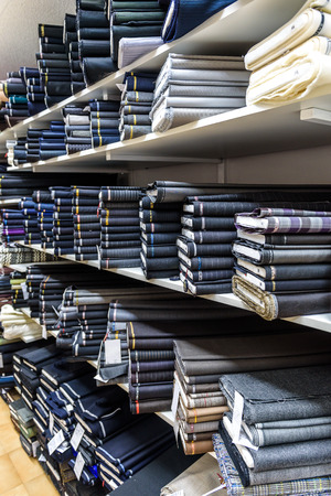 cotton fabric: Rolls of fabric and textiles in a factory shop or  store or bazar. Multi different fabric for men formal business suit on the market. Industrial fabrics.