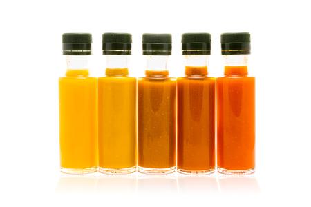 ホーム別の色は、ガラスびんのホットソースです。イエロー、ブラウン、マスタード、レッド色のバイオ エコ食材を使った冷たいソース。 写真素材