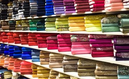 textil: Los rollos de tela y tejidos en una tienda de fábrica o tienda o bazar. Múltiples colores y diseños diferentes en el mercado. Telas industriales. Foto de archivo