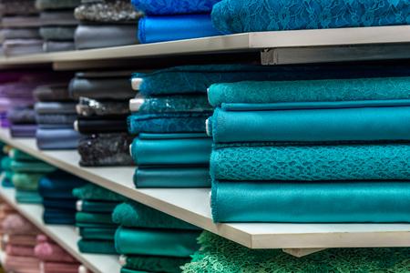 공장 상점 또는 상점 또는 바자르에서 직물의 롤 및 섬유. 시장에 다 다른 색상과 패턴. 기술 직물.