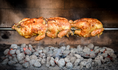 briquettes: Cooking 3 rotisserie chicken on the grill with Charcoal and Briquettes in the professional steak house or barbecue restaurant