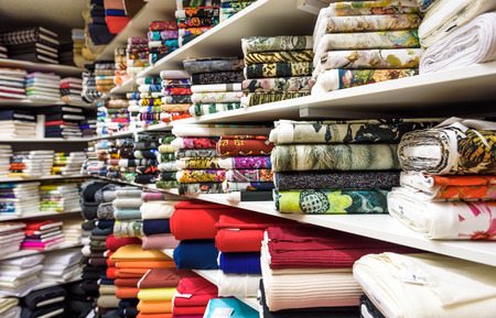 manufacturing materials: Rolls of fabric and textiles in a factory shop or  store or bazar. Multi different colors and patterns on the market. Industrial fabrics.