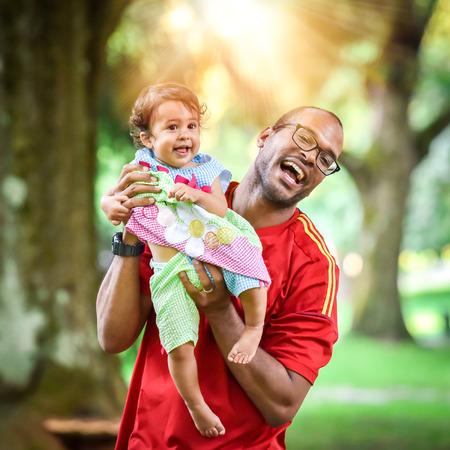 父と娘は遊んで、公園で笑っています。ムラートの赤ちゃんと一緒にアフリカ系アメリカ人やヒスパニック系の人はアクティブなゲームをプレイします。 写真素材 - 47471772
