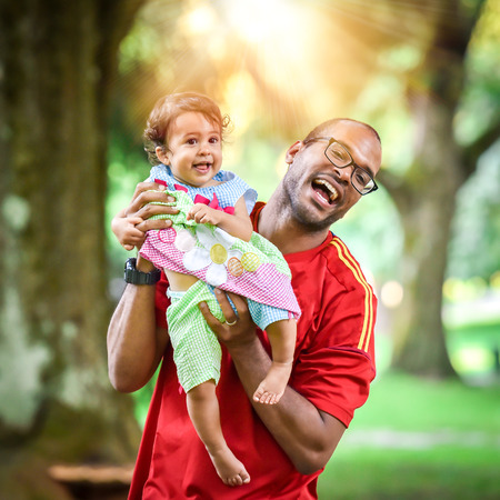 Father and daughter are playing and laughing in the park. African American or Hispanic man with mulatto baby is playing active game.
