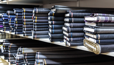 Rolls of fabric and textiles in a factory shop or  store or bazar. Multi different fabric for men formal business suit on the market. Industrial fabrics.