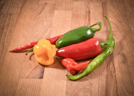 red jalapeno: Different Variety of chillies. Yellow Orange, Red lantern hot habanero and red and green jalapeno chili pepper from Caribbean or mexico. In wood desk Stock Photo