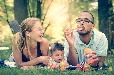 family outdoor: Happy interracial family is blowing bubbles  . Mixed diverse family is enjoying a day in the park. Mother father and mulatto son are smiling and are picnicking in the green park. Stock Photo