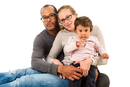 one family: African American Hispanic father, caucasian white mother and mulatto daughter are happy together. Mixed interracial diverse mixed family is looking at the camera. Stock Photo