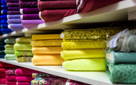 fabric roll: Rolls of fabric and textiles in a factory shop or  store or bazar. Multi different colors and patterns on the market. Industrial fabrics.