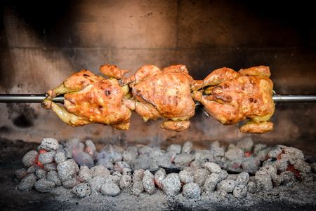 Cooking 3 rotisserie chicken on the grill with Charcoal and Briquettes in the professional steak house or barbecue restaurant